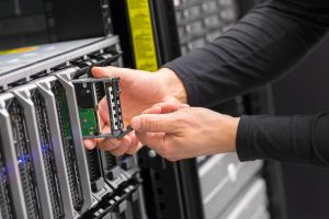 Close up of a IT engineer or consultant working with hard drive installation in a blade server. Data rack in a large datacenter.